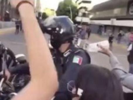 DICAS: Vídeo de manifestantes jogando um líquido e ateando fogo nas costas de um policial.