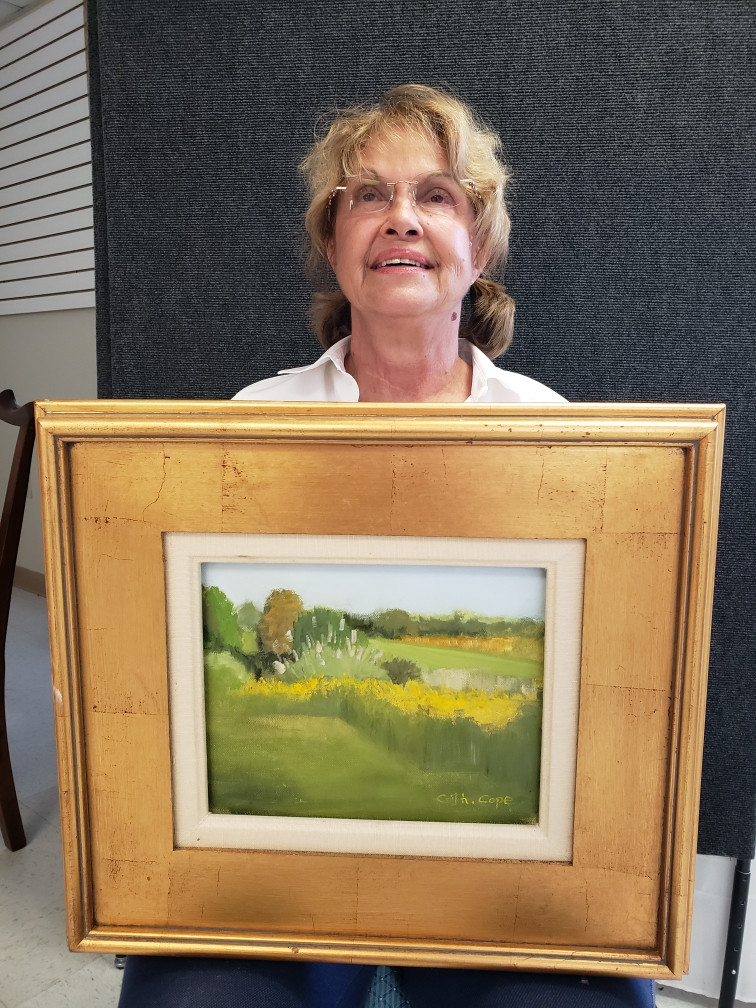 Pictured, Catherine Cope shows off her painting, Robert's Garden, created during the 2020 Pike Road Plein Air Paint Out.