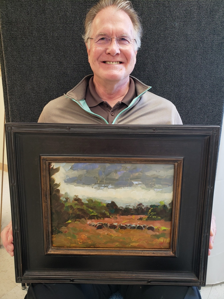 Pictured, Steve Barrington shows off his painting, Rittenour Road Stormy Skies, created during the 2020 Pike Road Plein Air Paint Out.