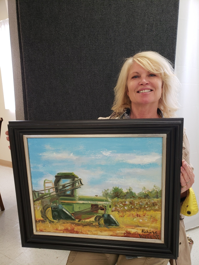 Pictured, Robine Wright shows off her painting, Bob's John Deere at Cotton Season, painted during the 2020 Plein AIr Paint Out.