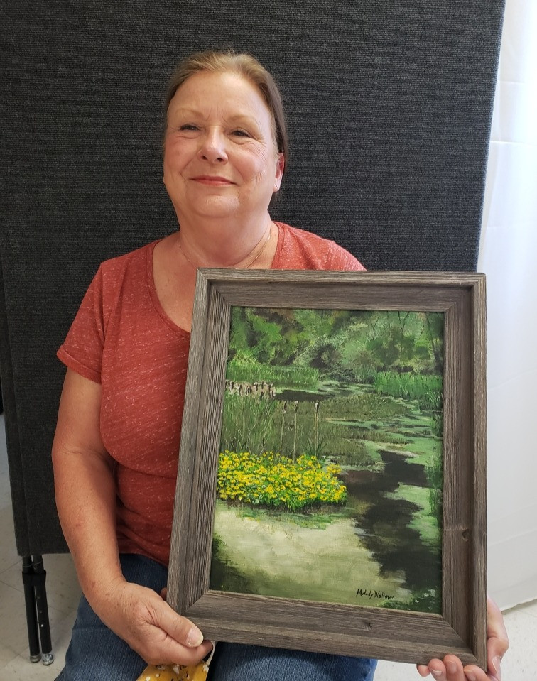 Pictured, Melody Waltman shows off her painting, Serenity at Ring Around Road, created during the 2020 Pike Road Plein Air Paint Out.
