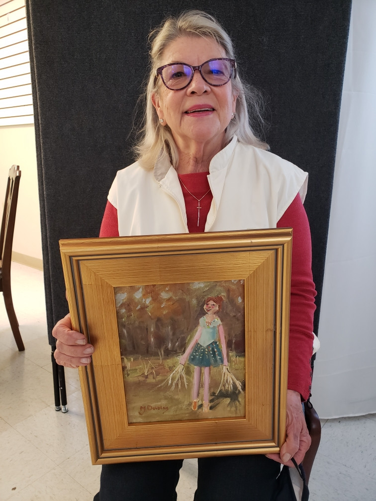 Pictured, MJ Dobbins shows off her painting, Ballerina Scarecrow, created during the 2020 Pike Road Plein Air Paint Out.