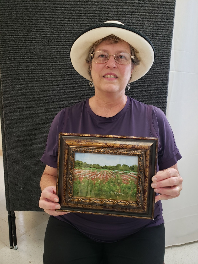 Pictured, Leslie Brasher shows off her painting, Pike Road Cotton, created during the 2020 Pike Road Plein Air Paint Out.