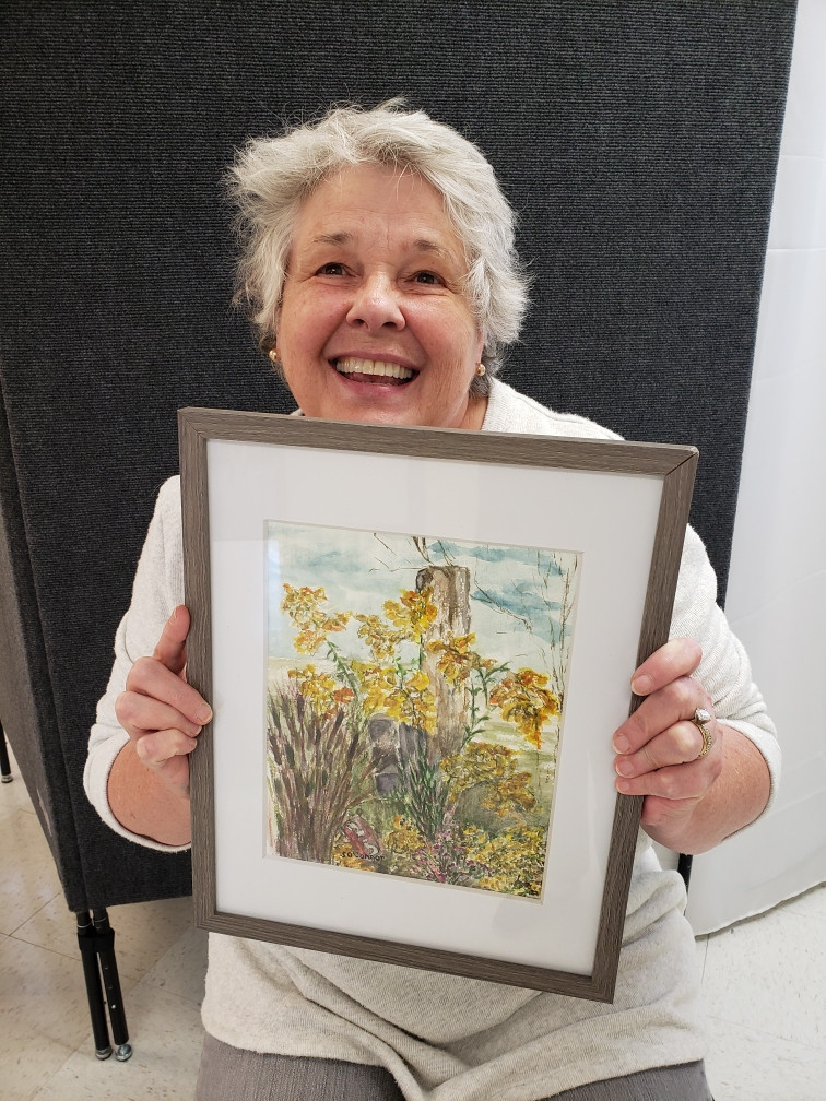 Pictured, Susan O'Connor shows off her painting, Goldenrods, created during the 2020 Pike Road Plein Air Paint Out.