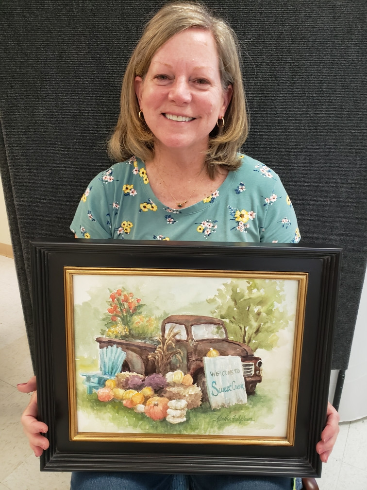 Pictured, Martha Fulghum shows off her painting, Fall at SweetCreek, created during the 2020 Pike Road Plein Air Paint Out.