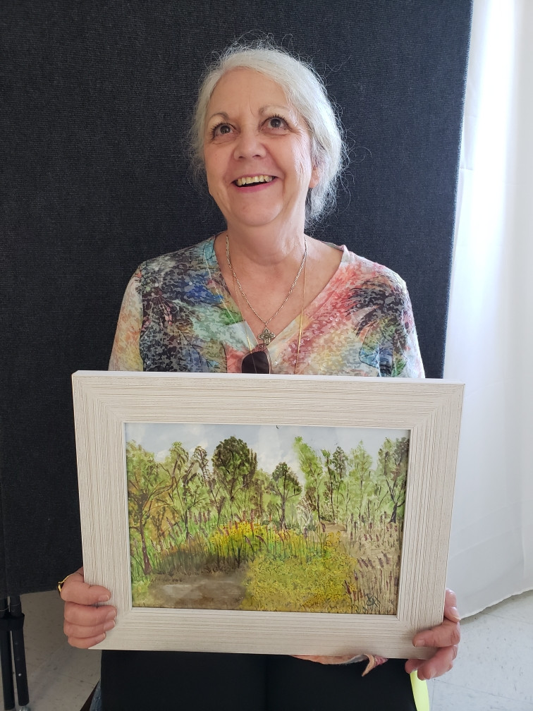Pictured, Patti Hemme shows off her painting, Preserve at The Waters, created during the 2020 Pike Road Plein Air Paint Out.
