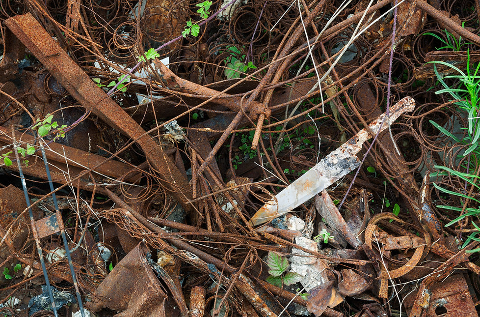 Burnt kitchen knife hidden in pile of waste rusted metal.