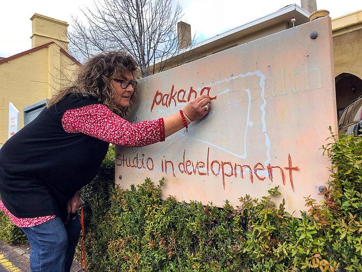 Cheryl writing on pakana studio sign