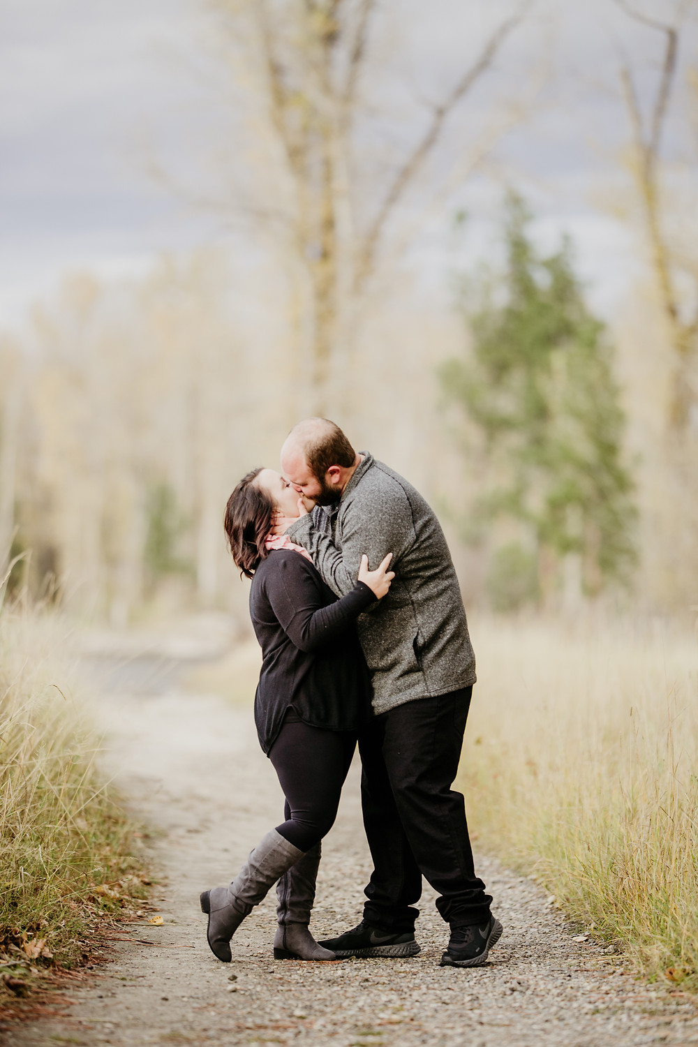couple kissing in the middle of a path in Stevensville, Montana during their engagement session