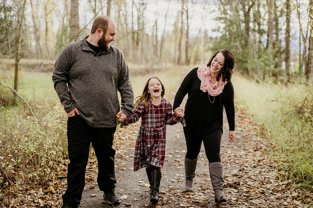 family with 6 year old daughter holding hands and laughing as they walk down the path