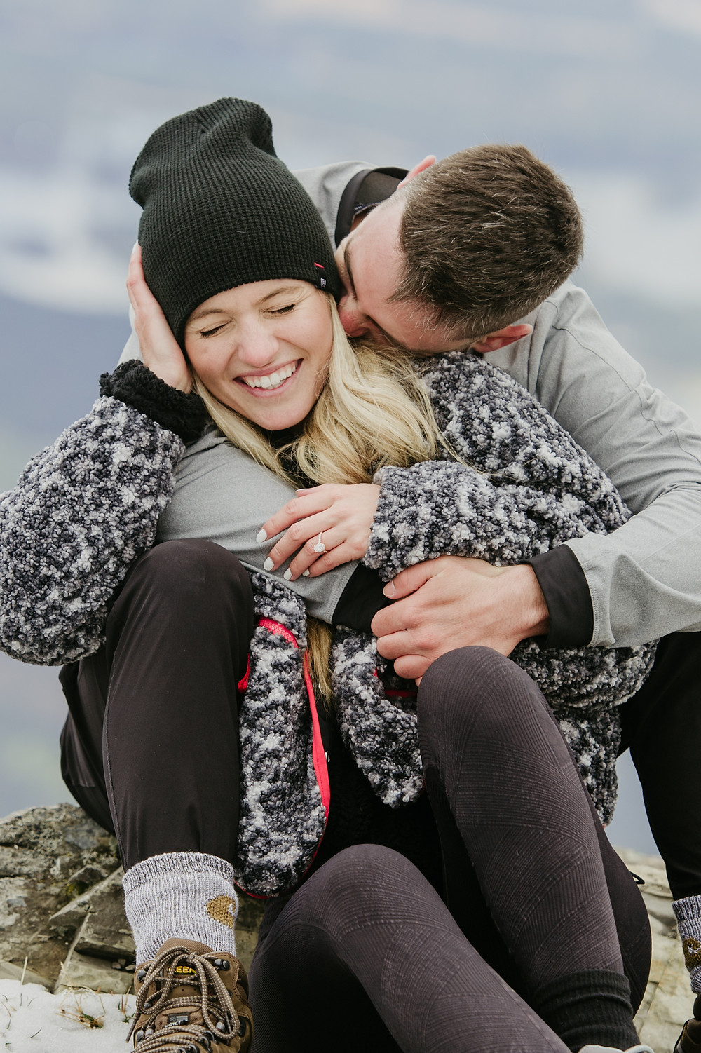 man and woman sitting closely together while man kisses woman and she is laughing