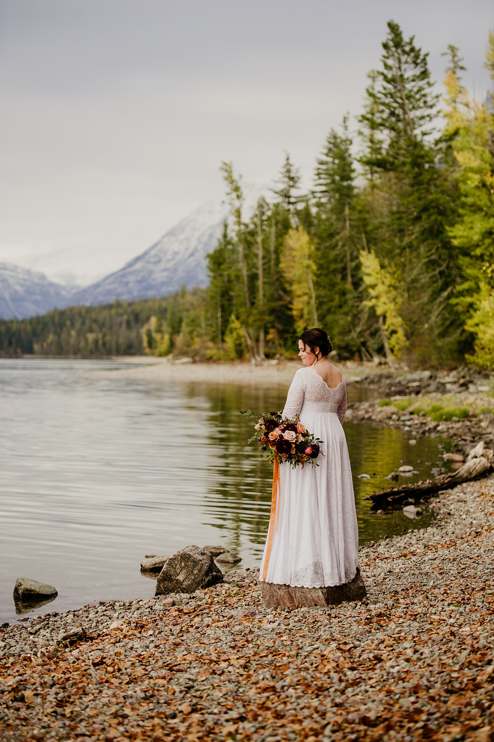 Bride standing on the shore of Lake McDonald in Glacier National Park
