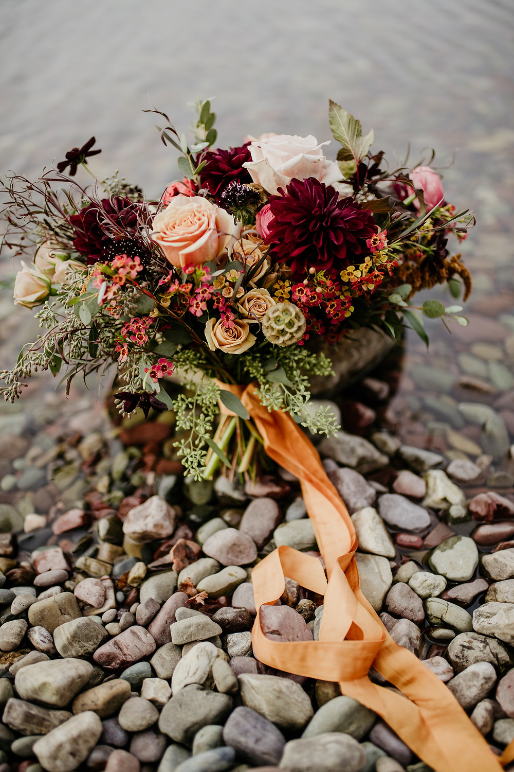 fall wedding bouquet with mustard silk ribbon on the shores of the water