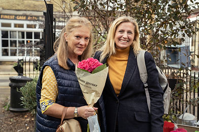 Two ladies outside a florist posing with a pink bunch of flowers