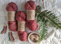 Several skeins of yarn from Knitting Niqabi, with natural elements around.