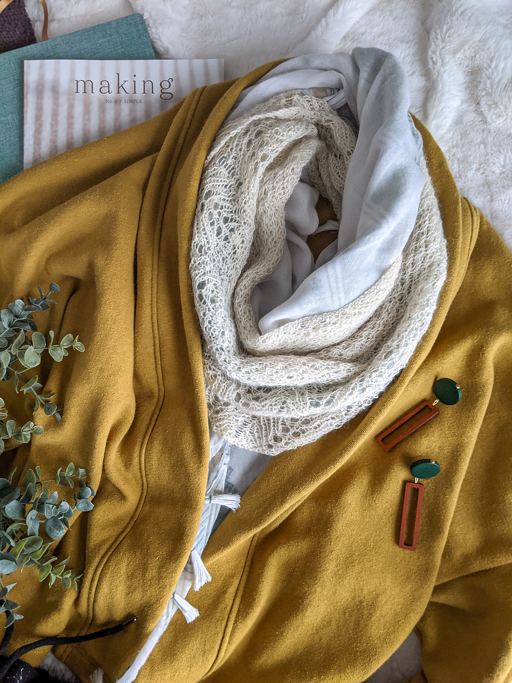 Delicate lace scarf layered with a gauze scarf, mustard fleece jacket.