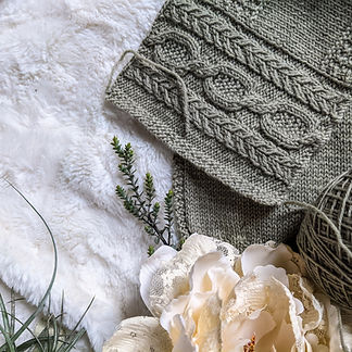 A swatch with soft gray green cables and a cream pink silk flower.