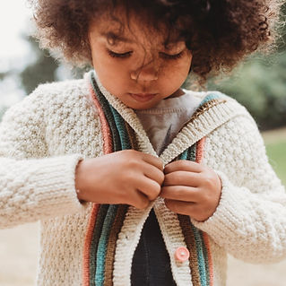 Mia buttons her Letters to Camp Sweater, a handknitting pattern for children.