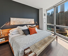 Designer bedroom in Chicago apartment with platform bed with city view and black accent wall
