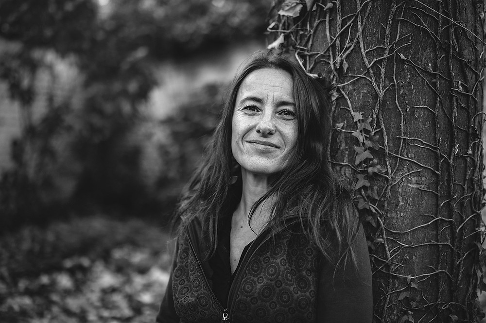 woman in her 50s smiling with a tree