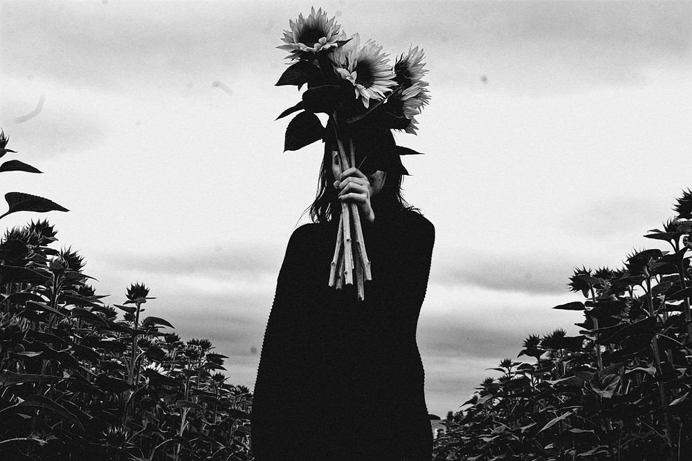 a woman hiding behind sunflowers