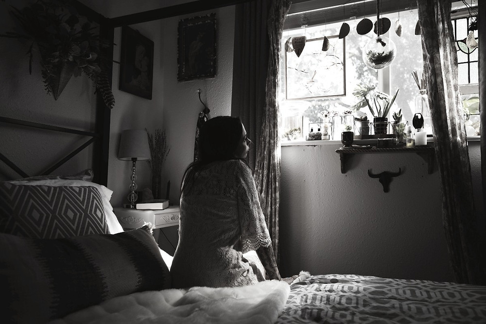 woman sitting on edge of a bed, gazing out of the window