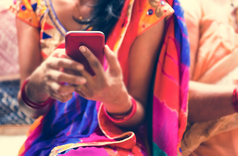 Female teenager in India using mobile phone.