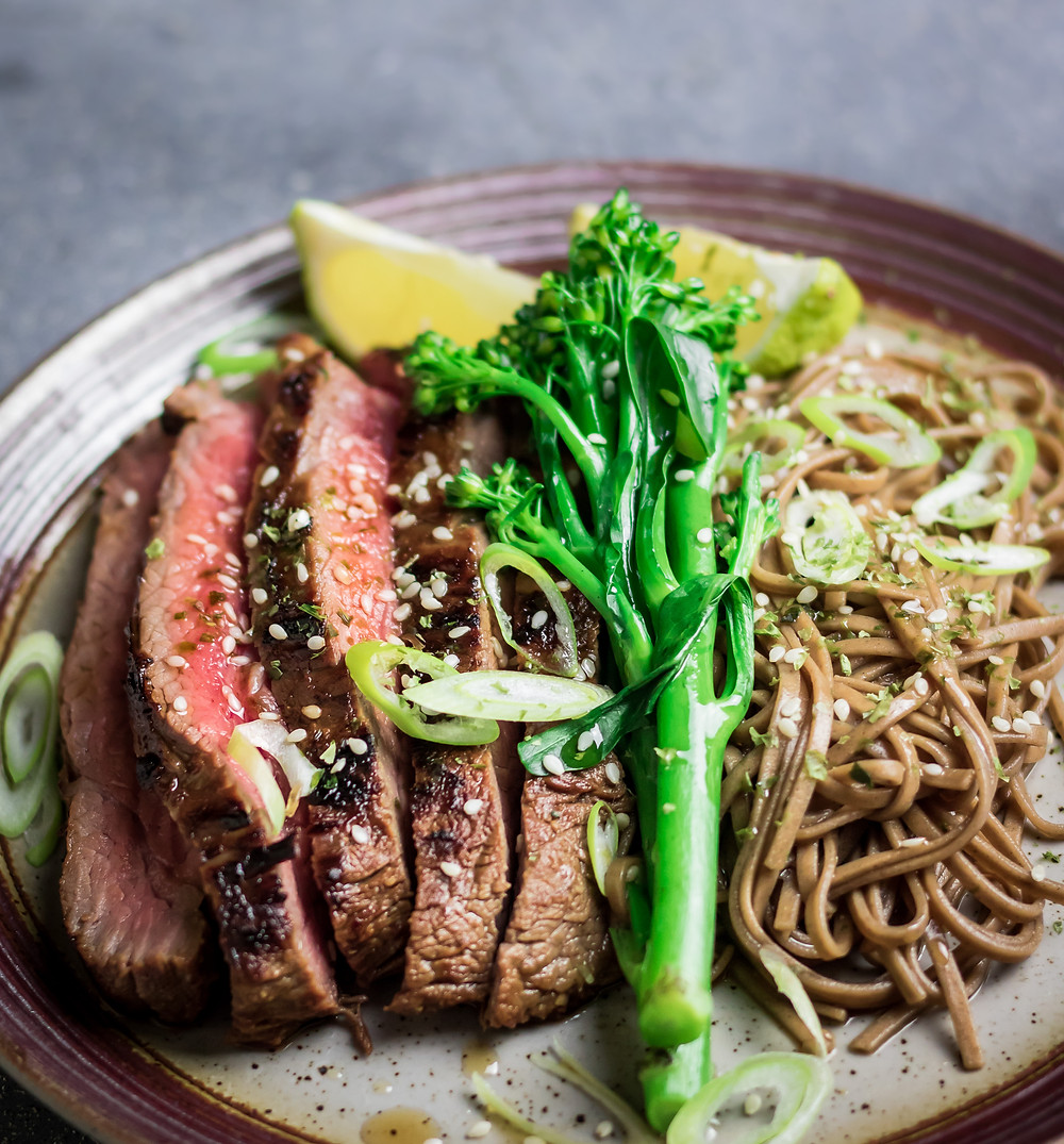 Medium rare Flank steak with vibrant tender-stem broccoli, Soba noodles and garnished with chopped spring onions, sesame seeds and lime wedges.
