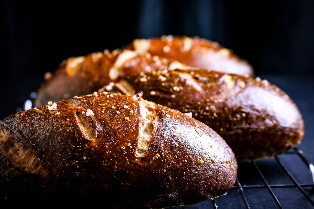 Front on horizontal view of golden brown football shaped pretzel loaves on a cooling rack and slat crystals on top
