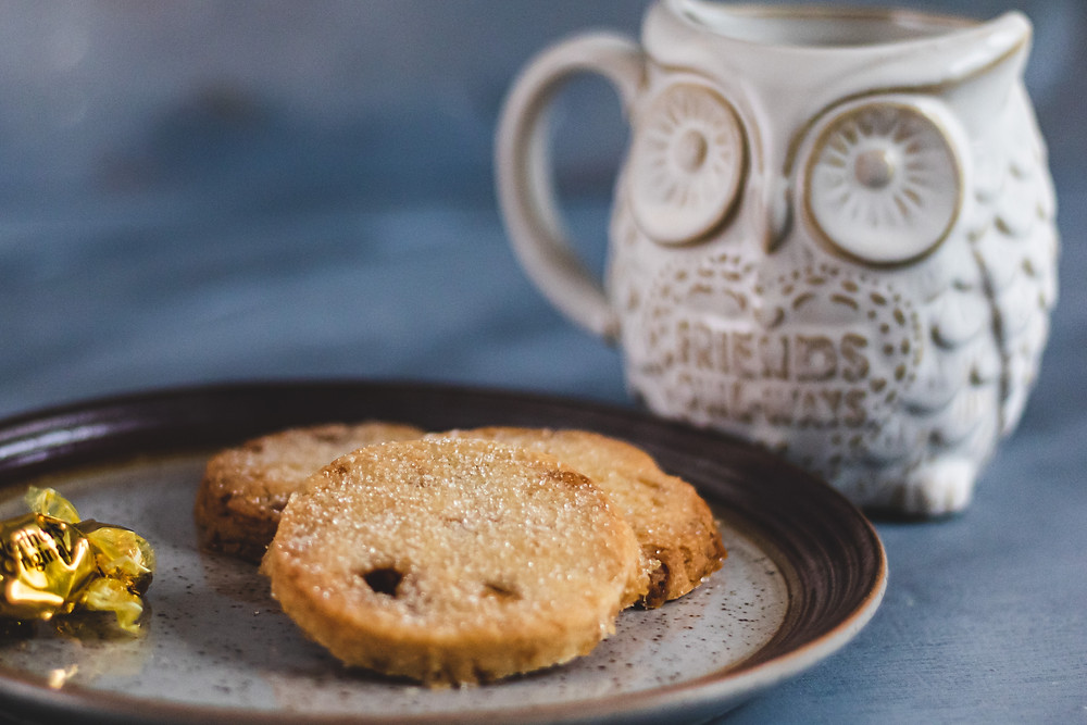 Shortbread cookies on a plate with Werther's original. Large Owl mug in the backrouind.