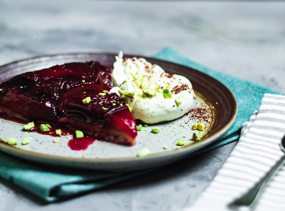 Ruby red Plum Tarte Tatin on a plate with mascarpone, crushed pistachios and sumac. The plate is sitting on a Teal cloth
