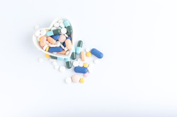Medication of the cup with white heart, Colorful medicine, Medicine and capsules on over white backg