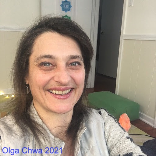 "Olga Chwa is looking at the camera, smiling. They have thin shoulder-length hair and are wearing a light gray vest over a white-and-black cardigan. Behind is their online teaching studio with a salt lamp, yoga bolster and chakra banner hanging on an open door. The photo is captioned ""Olga Chwa 2021."""