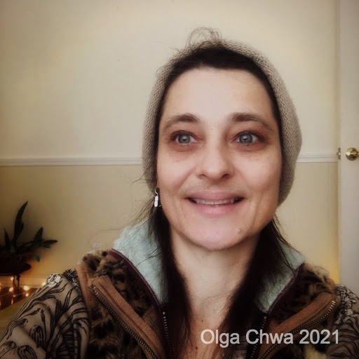 Olga Chwa's face and shoulders, they are wearing a beanie hat and looking slightly off to the side. There is a two-toned wall behind them. The photo is captioned 'Olga Chwa 2021'