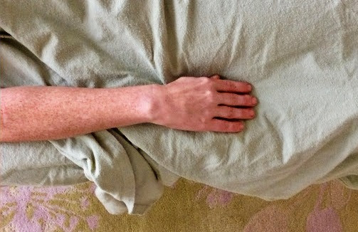 One bare hand and forearm rest over a flannel sheet at the edge of a massage table