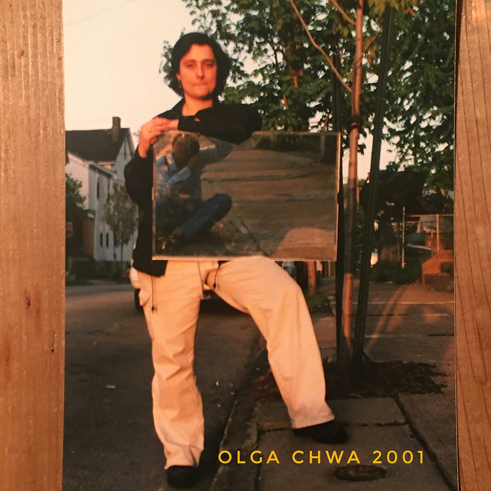 Olga Chwa is standing on a quiet city street with on foot up on the curb. She is holding a bathroom mirror, balanced on her thigh, which captures a reflection of the photographer, sitting on the sidewalk. Olga has short, messy hair and is wearing baggy beige cargo pants and a black jacket.  The photo is captioned 'Olga Chwa 2001'.