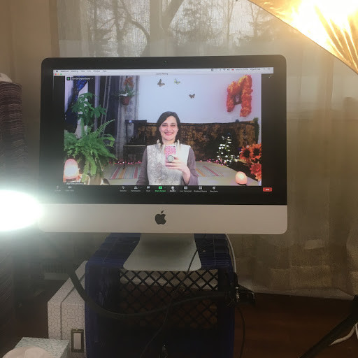 Olga Chwa is on a zoom screen in her teaching studio, effectively capturing the whole teaching space: computer in front, yoga mat in the back
