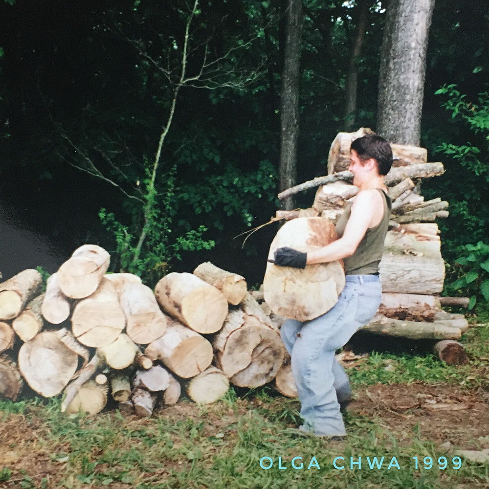 Olga Chwa is carrying a 2-foot long, 18-inch diameter log towards a pile of logs on the ground, at the edge of a wooded treeline. She has short dark hair and is wearing a dark green tank-top, loose, faded jeans and black gloves. The photo is captioned 'Olga Chwa 1999'.'