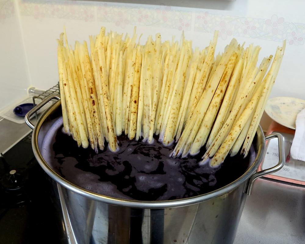 染料が入った寸胴鍋に竹皮を入れる