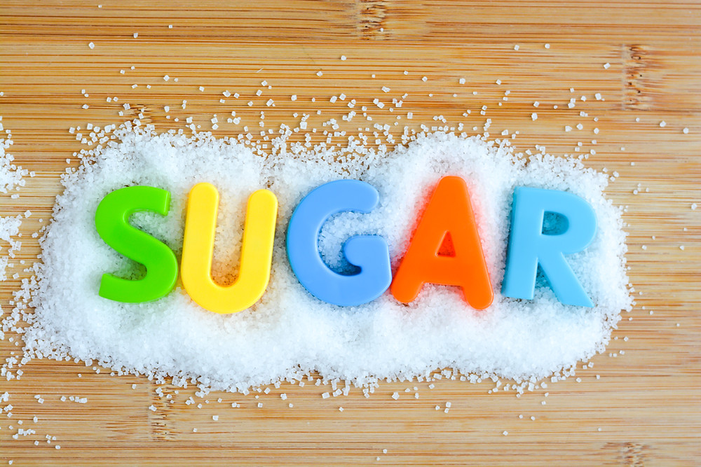 Letters to spell out SUGAR on a pile of sugar