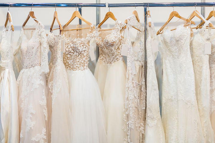 Many beautiful wedding dresses hang in t