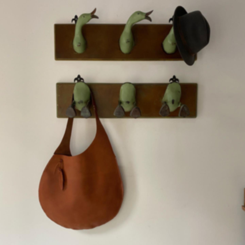 Circular brown leather tote on wall