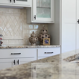 white kitchen with stone backsplah.webp