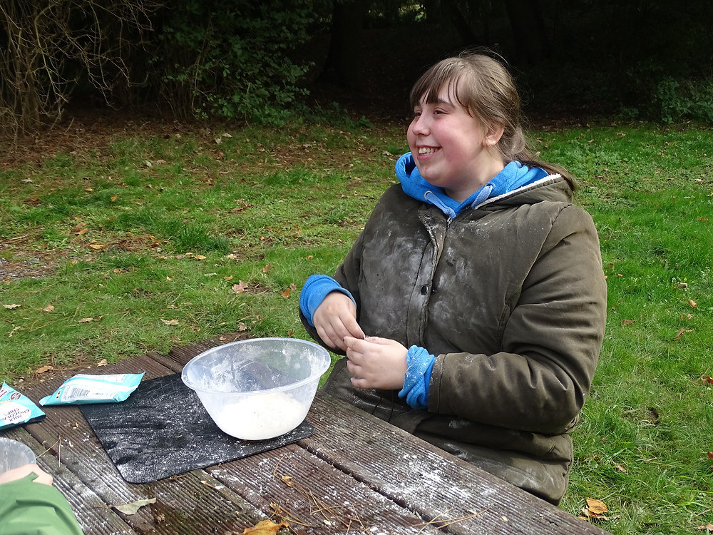 Student making dough in the woods with a smile on her face.