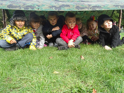 8 children sat under a shelter they have built