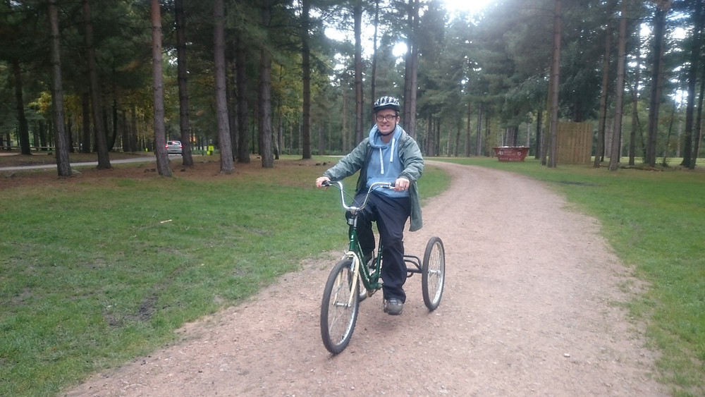 A service user riding a tricycle at Sherwood Pines.