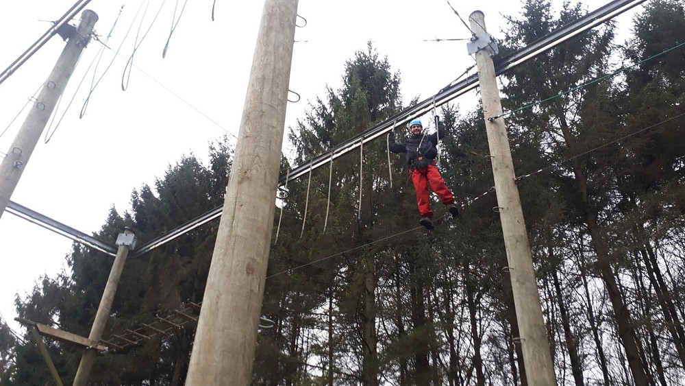 An individual in red trousers and a blued helmet on a high ropes course