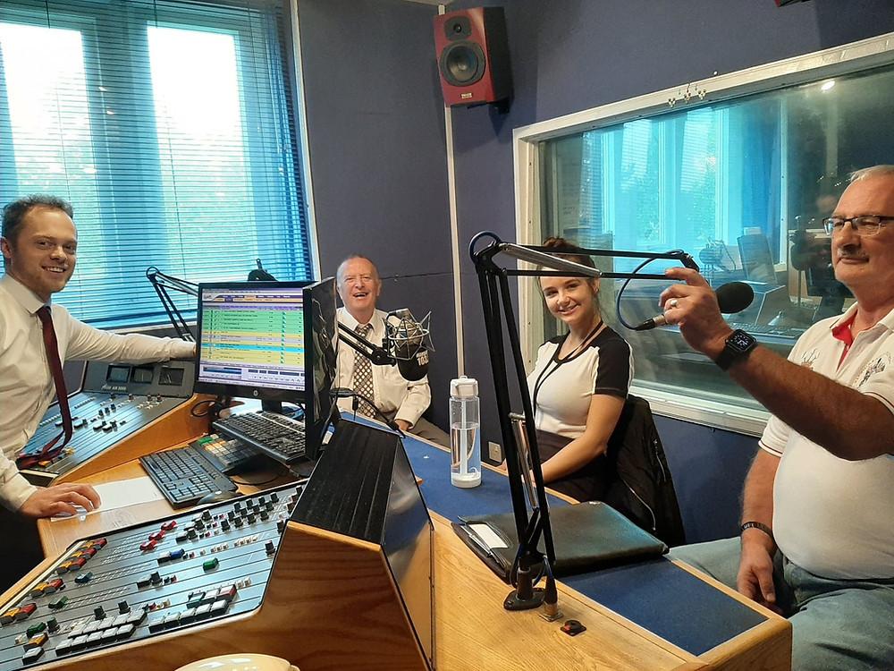 Four individuals in a radio recording studio.