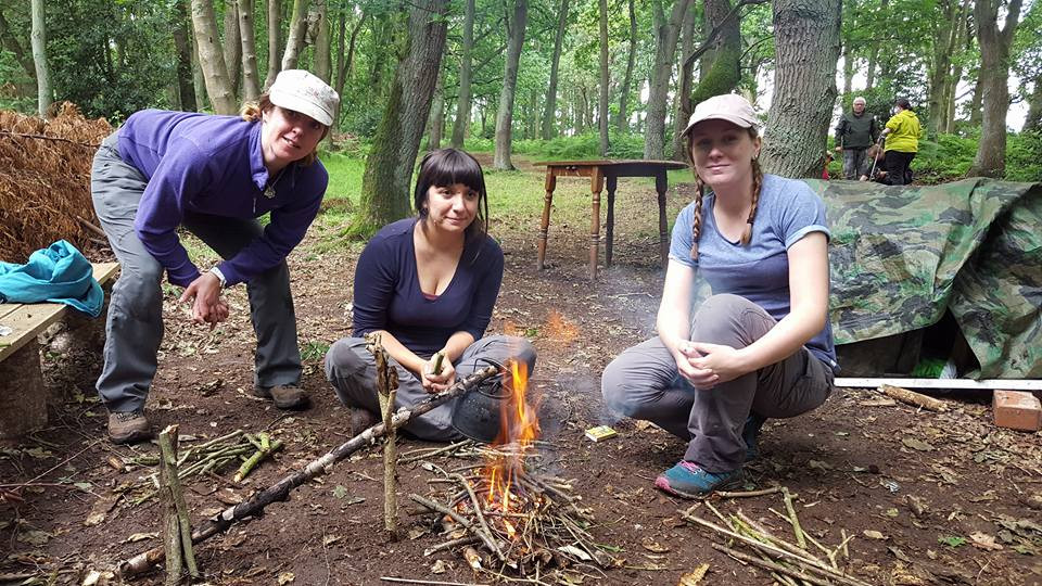 Three ladies/members of staff, sat around a fire