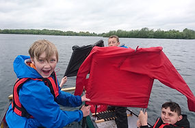 three boys on a canoe on open water, sailing and smiling